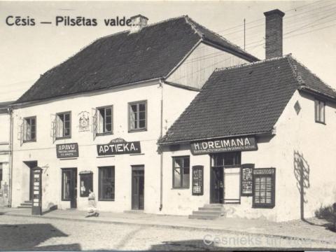 Namā Rīgas ielā 7 atradās Cēsu pilsētas valde, pilsētas aptieka un uzņēmēji: tirgotājs un kurpnieks Ed. Amats, grāmatnieks H. Dreimanis, 20. gs. 30. gadi; CM 63345