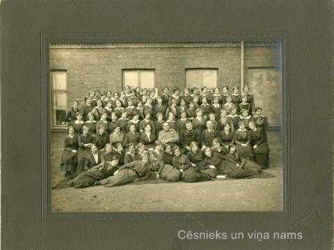 """K. Apkalnes sieviešu ģimnāzijas audzēknes un skolotāji; otrajā rindā no kreisās puses 6. - Kristīne Apkalne, ap 1911. gadu. Foto """"Brāļi Matīsi Rīgā un Cēsīs"""" - CM 59104"""