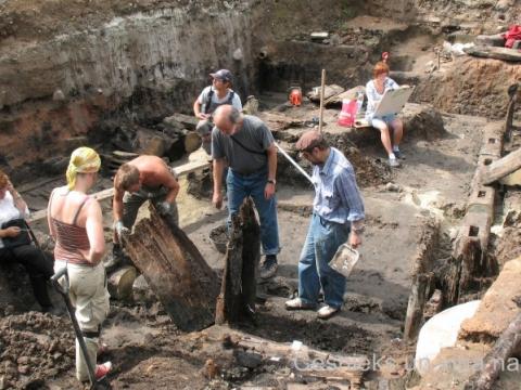Izrakumu laukums 2008.g. 15. jūlijā Rožu laukumā, senajā Tirgus laukumā. Zem asfalta seguma, 2,4 m dziļumā, arheologi atraka koka ēkas pagrabstāvu. Dendrohronoloģiskā datēšana uzrādīja, ka ēka celta ap 1281. g. - D. Cepurītes foto