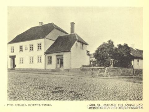 No Rīgas ielas puses, koku ieskauts, redzams Bergmaņa mājas gals. L. Borevica uzņēmums 20. gs. sākumā.