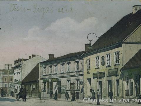 Cēsnieki Rīgas ielā 20. gs. sākumā. Vislabāk redzama grāmatizdevejā J. Ozola tipogrāfijas izkārtne.