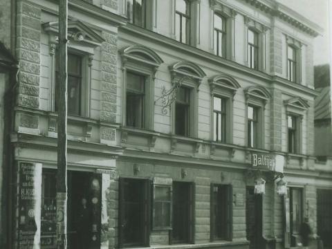 """Ēka Cēsīs, Rīgas ielā 21 - kreisajā pusē H. Kuzmana pilksteņu veikala un darbnīcas izkārtne, virs ieejas viesnīcā izkātne """"Baltijas Viesnica"""" un laternas abpus durvīm, 1920. gadu beigas-1930. gadu sākums. Foto no E. Šneiderāta f"""