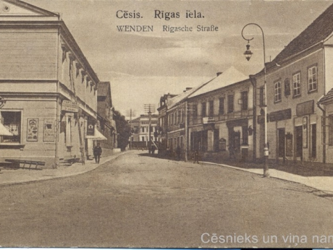 """1918. gadā pastkartes izdeva gan zaļganā, gan brūnganā tonī. Uz nepārdotajām pastkartēm izdevējs vēlāk iespieda nosaukumu latviski """"Cēsis. Rīgas iela""""; CM 52492"""