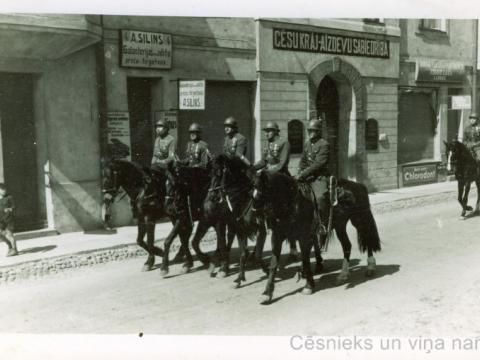 Karavīri zirgos pie Cēsu Krājaizdevu sabiedrības nama Rīgas ielā 4, 20. gs. 20. gadu vidus; CM 56359