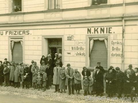 Cēsnieki sapulcējušies uz ietves pie nama Cēsīs, Rīgas ielā 6, ap 1930. - 1935. gadu.