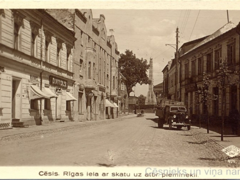 Nams Rīgas ielā 4, pie M. Radziņa veikala skatloga piestiprināta Valsts elektrotehniskās fabrikas (VEF) reklāma, 20. gs. 30. gadi; CM 112898